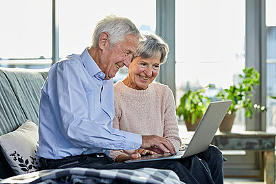 Senior couple sitting together on couch using laptop - p300m2081161 by Rainer Berg
