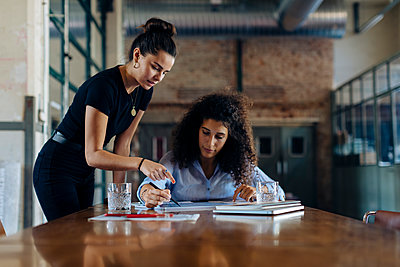 Two young businesswomen talking at conference table in loft office - p300m2144442 by Sofie Delauw