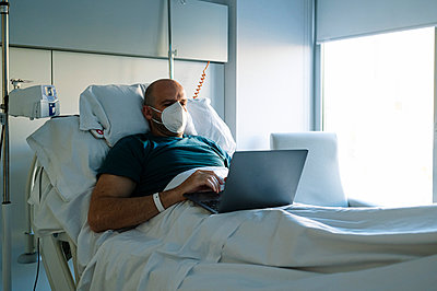 Male patient wearing face mask working on laptop while sitting on bed at hospital - p300m2242844 by Jose Luis CARRASCOSA