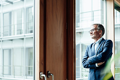 Thoughtful man with arms crossed looking through window in office - p300m2266351 by Gustafsson