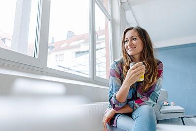 Junge Frau trinkt ein Glas Tee - p586m1510354 von Kniel Synnatzschke