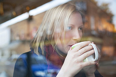 Woman drinking cup of coffee in cafe - p924m807262f by Sydney Bourne
