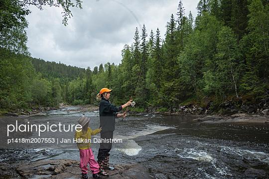 Junge Frau angelt mit ihrer Tochter - p1418m2007553 von Jan Håkan Dahlström