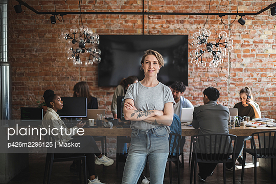 Female entrepreneur standing with arms crossed while colleagues working in creative office - p426m2296125 by Maskot