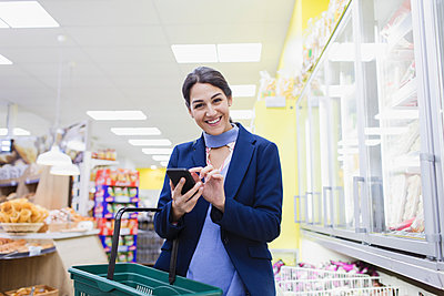 Portrait smiling, confident woman with smart phone shopping in supermarket - p1023m2187651 by Sam Edwards