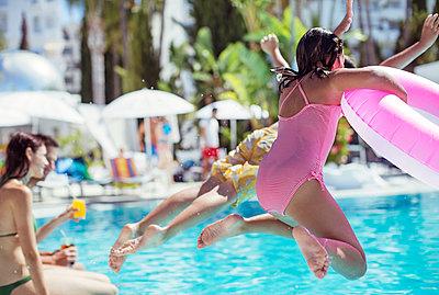 Children jumping into resort swimming pool - p1023m976795f by Paul Bradbury