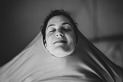 Woman in selfquaratine, Pulling sweater over her head - p1295m2173181 by Katharina Bauer