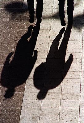 Shadow of two men walking in street - p1418m1571647 by Jan Håkan Dahlström
