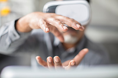 Man shaping with his hands wearing VR glasses in office - p300m1549842 by zerocreatives