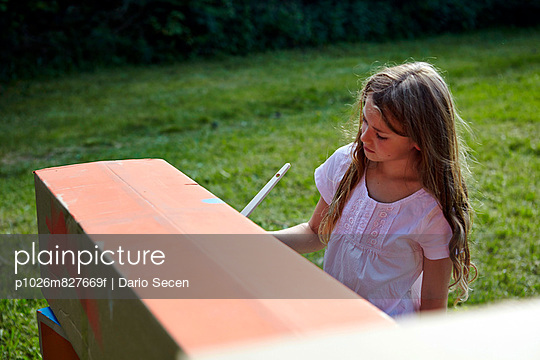 Girl painting cardboard box, Munich, Bavaria, Germany