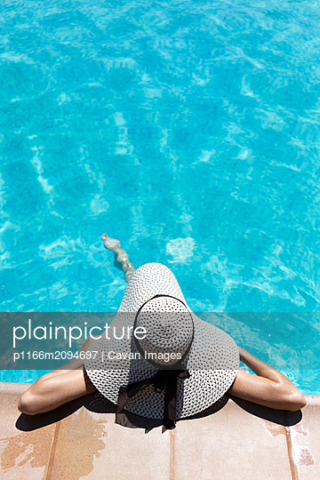 Unrecognisable woman relaxing in the swimming pool - p1166m2094697 by Cavan Images