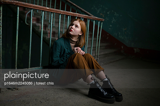 Teenage girl with red hair sitting in the staircase - p1646m2245086 by Slava Chistyakov