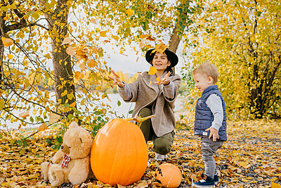 Happy mother and son playing with autumn leaves in park during Halloween - p1166m2068104 by Cavan Images