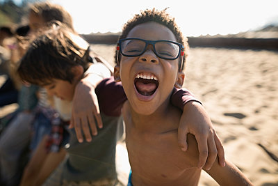 Portrait playful boy in eyeglasses screaming on sunny beach - p1192m1511887 by Hero Images