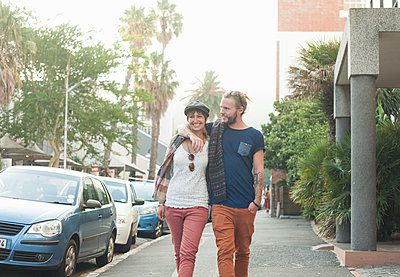 Couple walking with arm around on street - p300m2224982 by LOUIS CHRISTIAN