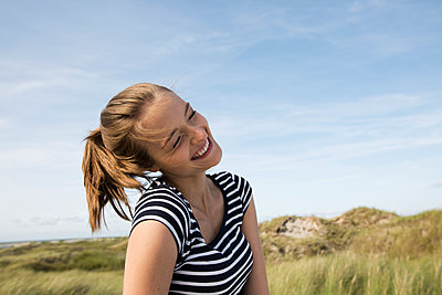 Young woman on beach with its dunes - p341m1480680 by Mikesch
