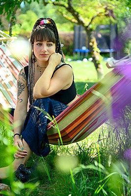 Nachdenkliche junge Frau in einer Hängematte - p427m2203610 von Ralf Mohr