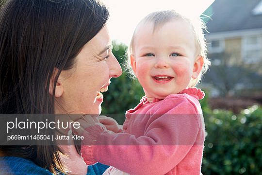 Mother Holding Baby Girl Outdoors - p669m1146504 by Jutta Klee photography