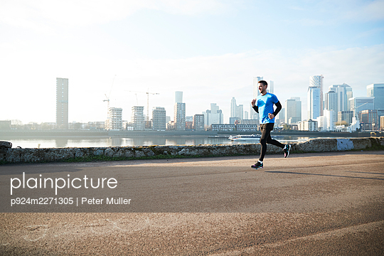 UK, London, Jogger running with downtown skyline in background - p924m2271305 by Peter Muller