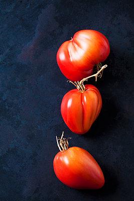 Three Oxheart tomatoes on dark background - p300m2079284 by Dieter Heinemann