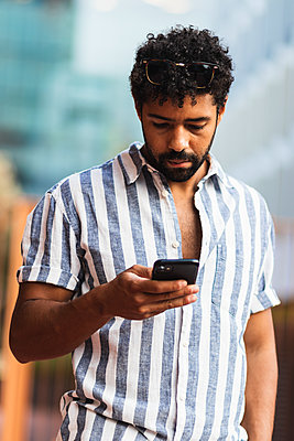 Man using smart phone while standing in city - p300m2226451 by NOVELLIMAGE