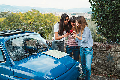Friends using smartphone in countryside, Florence, Toscana, Italy - p429m2097521 by Lorenzo Antonucci