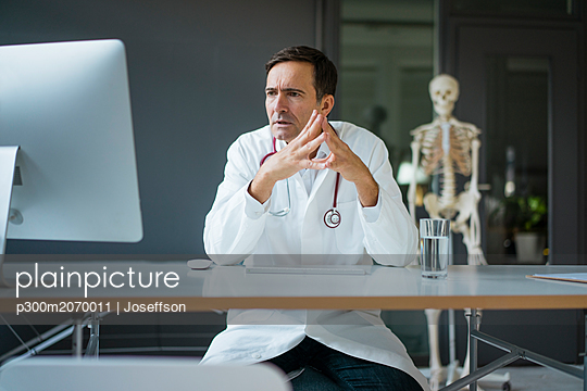 Serious doctor sitting at desk in medical practice with skeleton in background - p300m2070011 by Joseffson