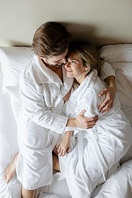Affectionate couple in bathrobes relaxing on hotel bed, enjoying romantic weekend - p1192m2047359 by Hero Images