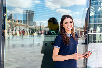 UK, London, portrait of smiling woman with smartphone in the city - p300m1499563 by Marco Govel