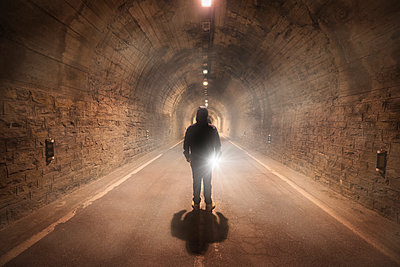 Spain, Huesca, young man exploring a dark tunnel - p300m1535592 by David Herraez Calzada