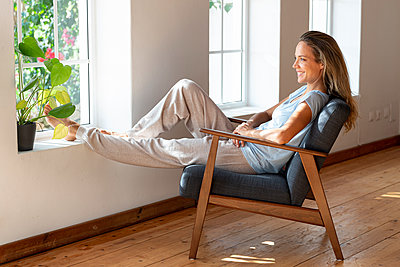 Happy beautiful woman looking away while sitting in living room - p300m2276387 by Steve Brookland