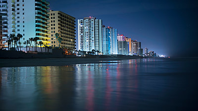 Illuminated buildings by beach in city at night, Daytona, Florida, USA - p301m1498818 by Brian Caissie
