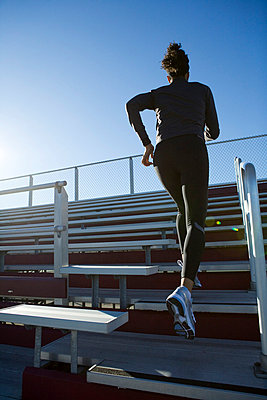 Woman running up grandstand - p3722405 by James Godman