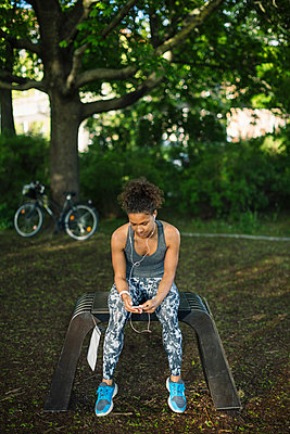 Woman sitting on bench listening music in park - p426m1085376f by Maskot