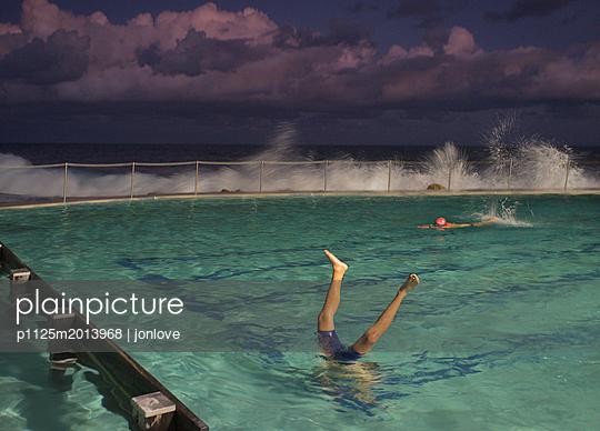 Man doing handstand in ocean pool - p1125m2013968 by jonlove