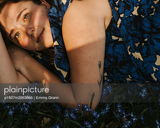 Woman lies in a sea of flowers - p1507m2263866 by Emma Grann