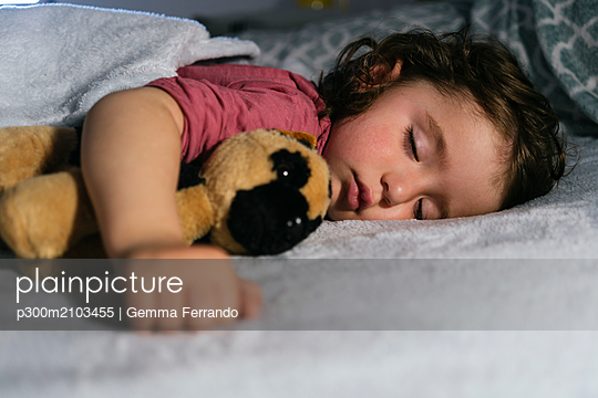 Portrait of toddler girl sleeping in bed  with a soft toy dog - p300m2103455 by Gemma Ferrando