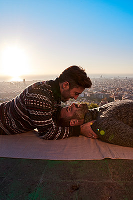 Romantic gay couple looking at each other while lying on viewpoint against clear sky, Bunkers del Carmel, Barcelona, Spain - p300m2256690 by Veam