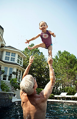 Man playing with granddaughter in pool - p429m768188 by Robyn Breen Shinn