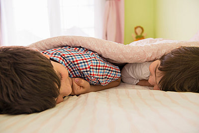 Brother and sister lying on bed - p924m805792f by Florin Prunoiu