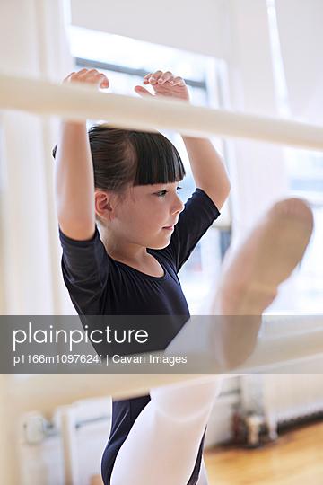 Little ballet dancer (6-7) practicing in studio