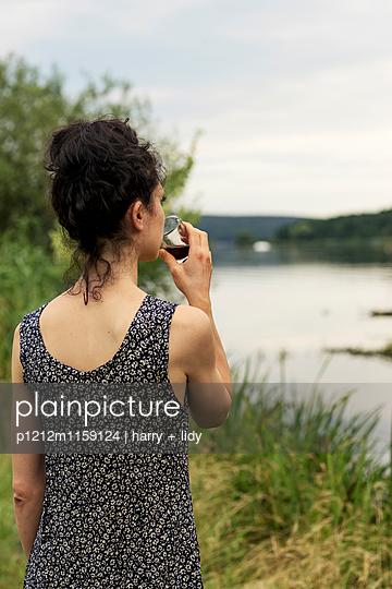 Junge Frau mit einem Glas Wein am Ufer - p1212m1159124 von harry + lidy