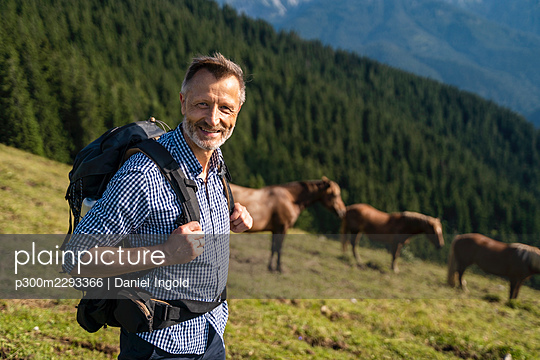 Smiling male hiker with backpack standing on mountain - p300m2293366 by Daniel Ingold