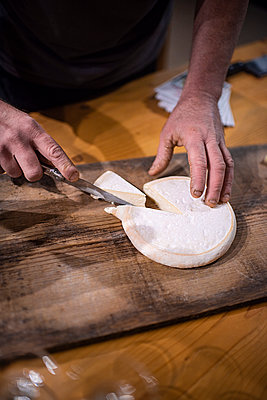 Man slicing traditional reblochon cheese - p1007m2216566 by Tilby Vattard
