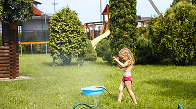 Little girl playing with water in the yard of the house - p1166m2159380 by Cavan Images