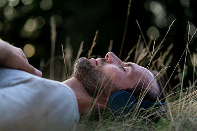 Relaxed man lying in field listening to music with headphones - p300m2042052 von harrylidy