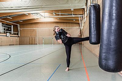Female kickboxer practising at punchbag in sports hall - p300m2144839 von Stefanie Baum
