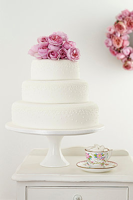 Three tiered wedding cake with pink floral arrangement and cup and saucer - p429m803089f by BRETT STEVENS