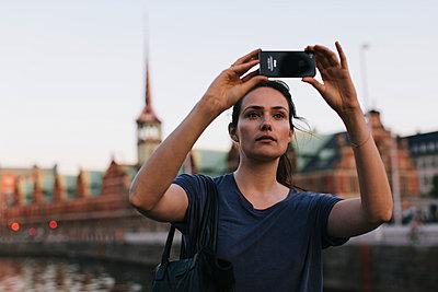 Junge Frau macht Fotos mit dem Smartphone - p586m952015 von Kniel Synnatzschke