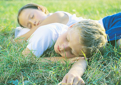 Boy and girl sleeping in grass - p6236486f by Laurence Mouton